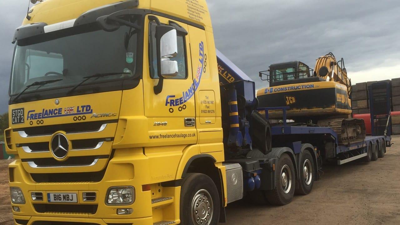 low loader hauling jcb digger