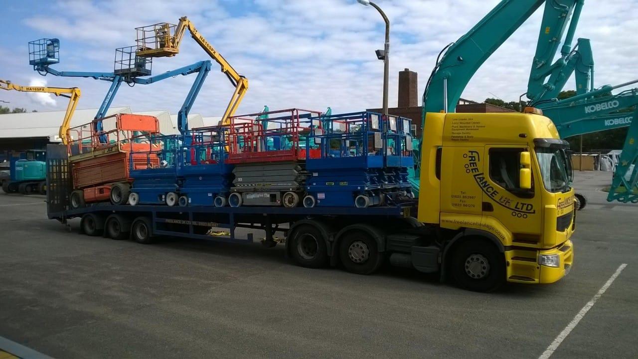 scissor lifts on low loader truck
